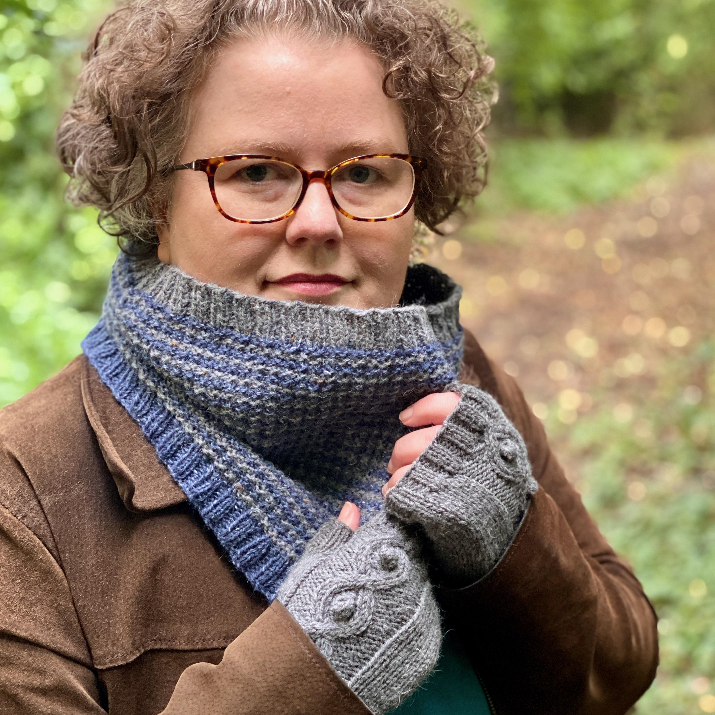 Hannah wearing trudy cowl knitted in dark sea blue and light grey wand pair of grey diamond mitts