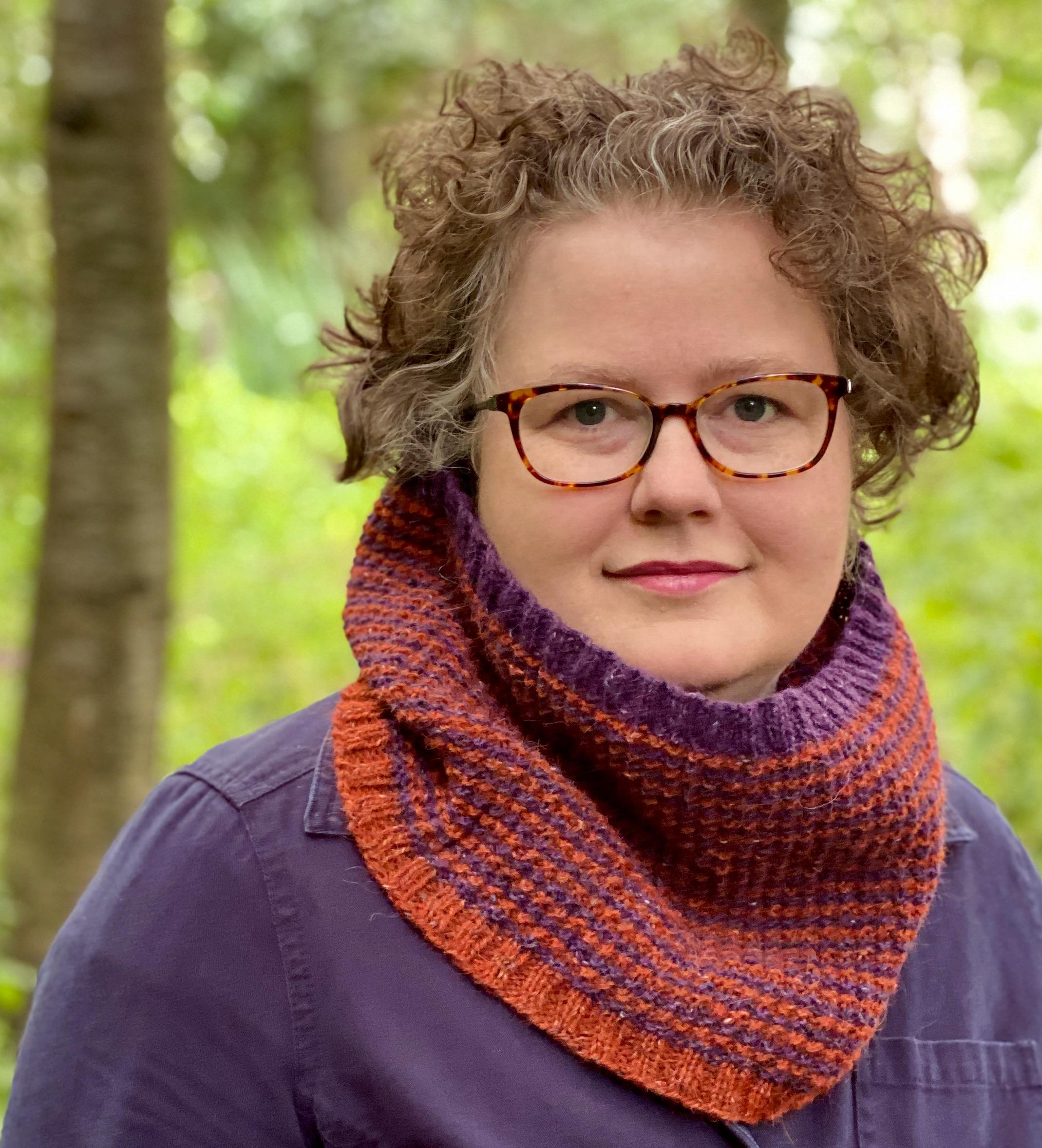 Hannah wearing a hand knitted Trudy cowl, striped in purple and orange