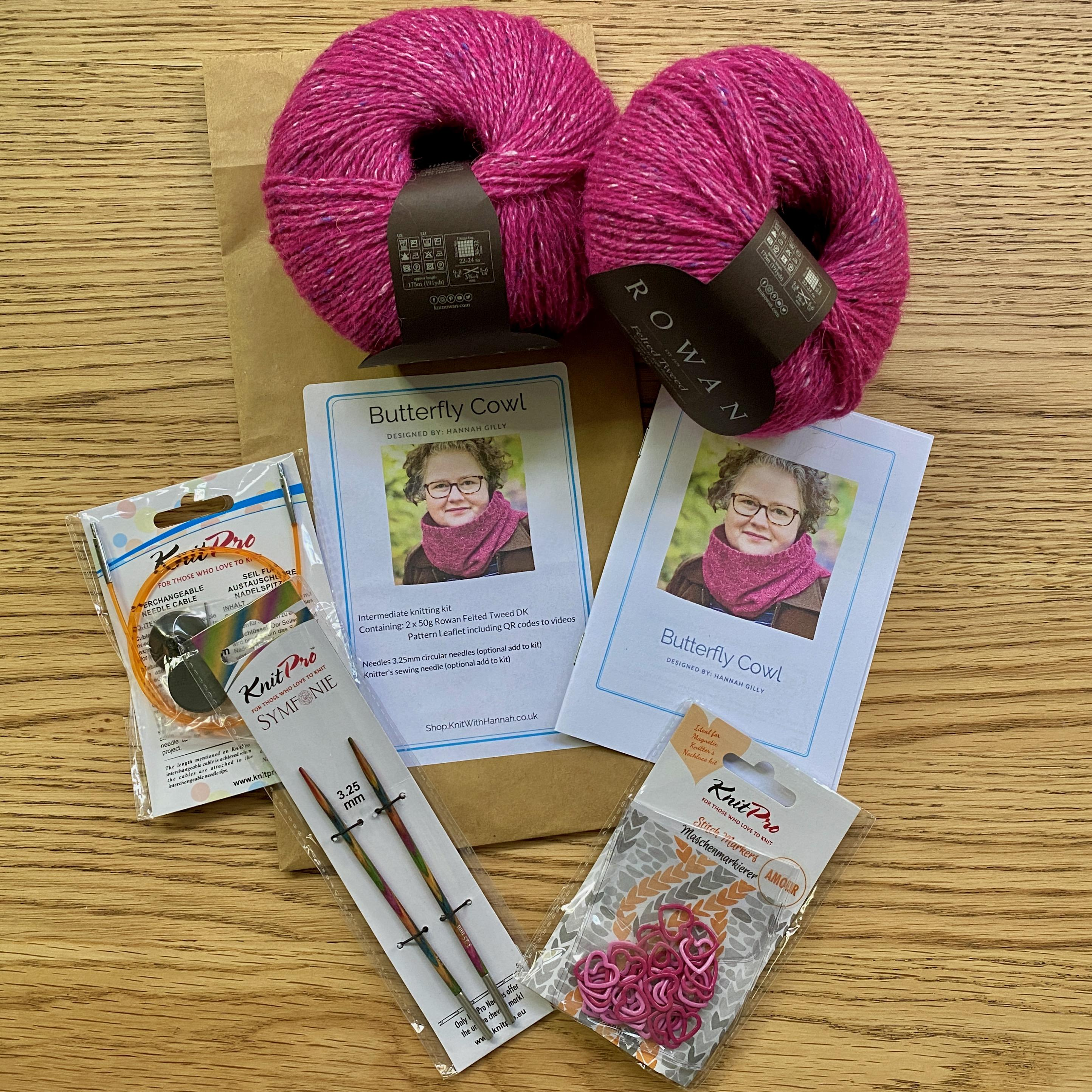 Open butterfly knitting kit on wooden table, pattern, pink yarn, knitting needles and stitch markers