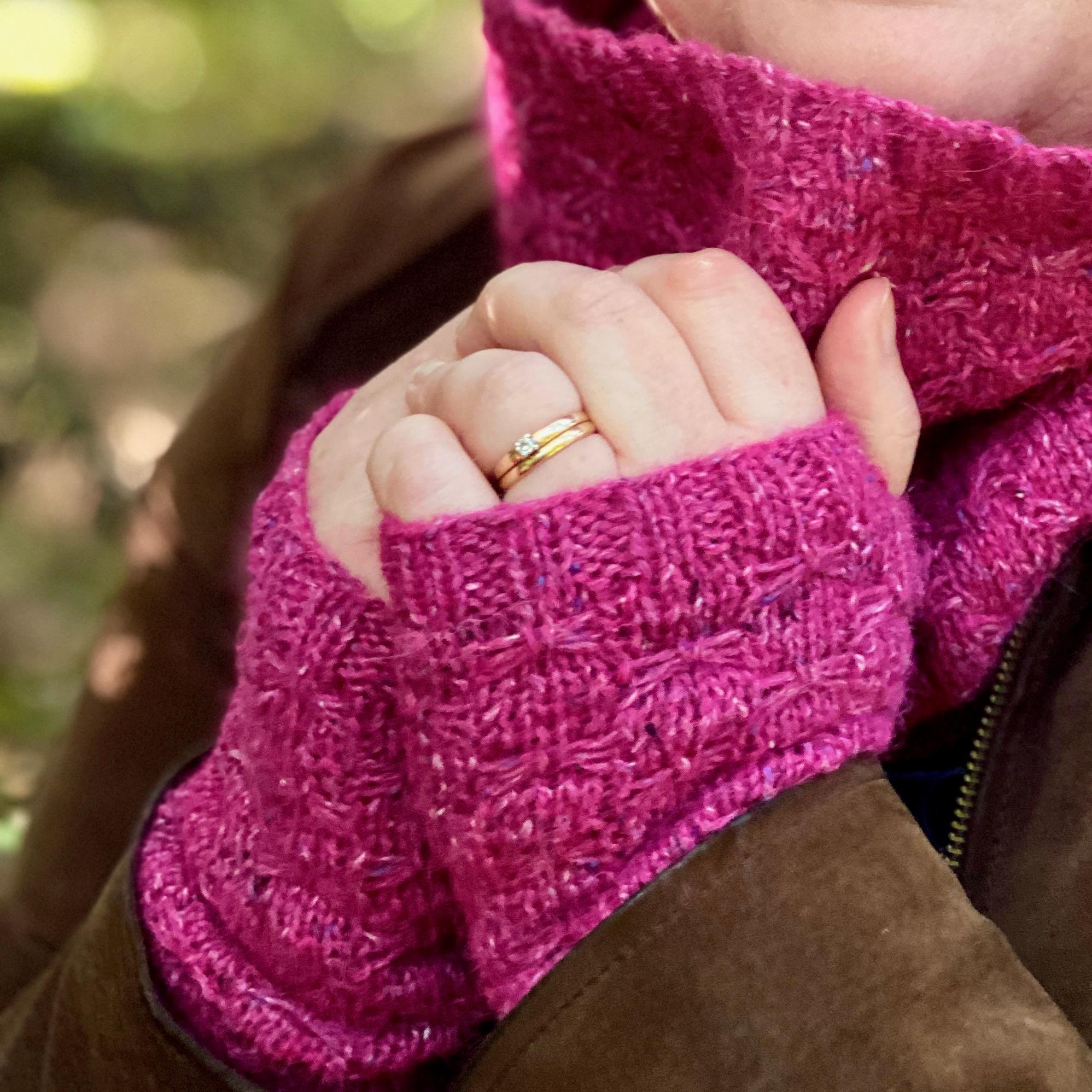 Hands wearing pink cuffs, holding cowl near face