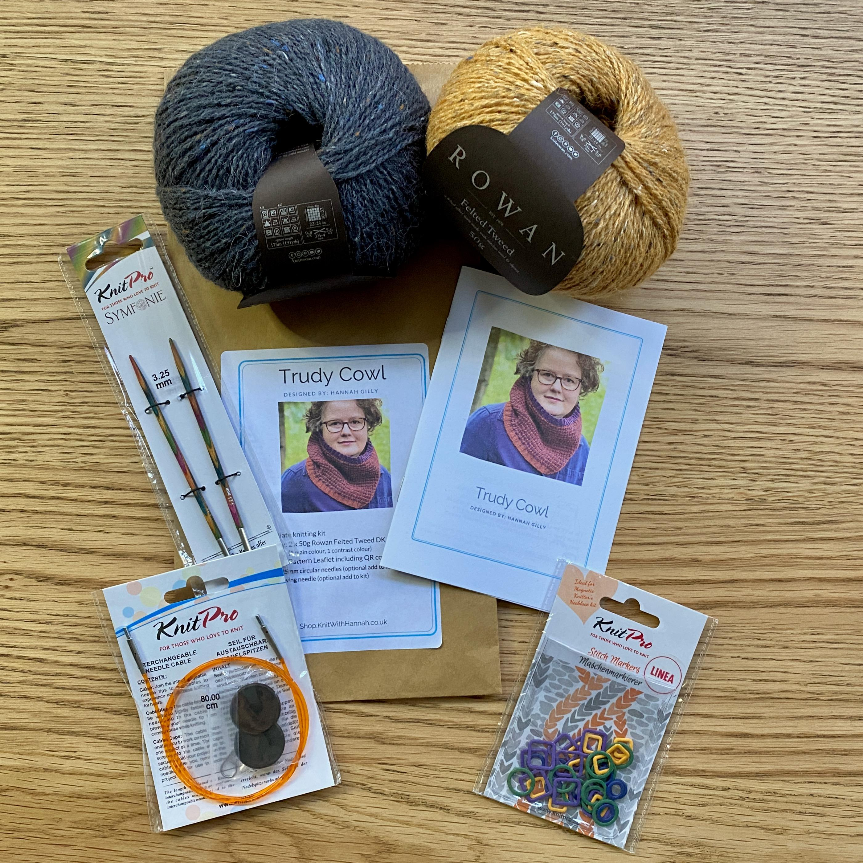 Turdy Cowl Knitting Kit open on wooden table, with bamboo knitting needles, and pink heart stitch markers