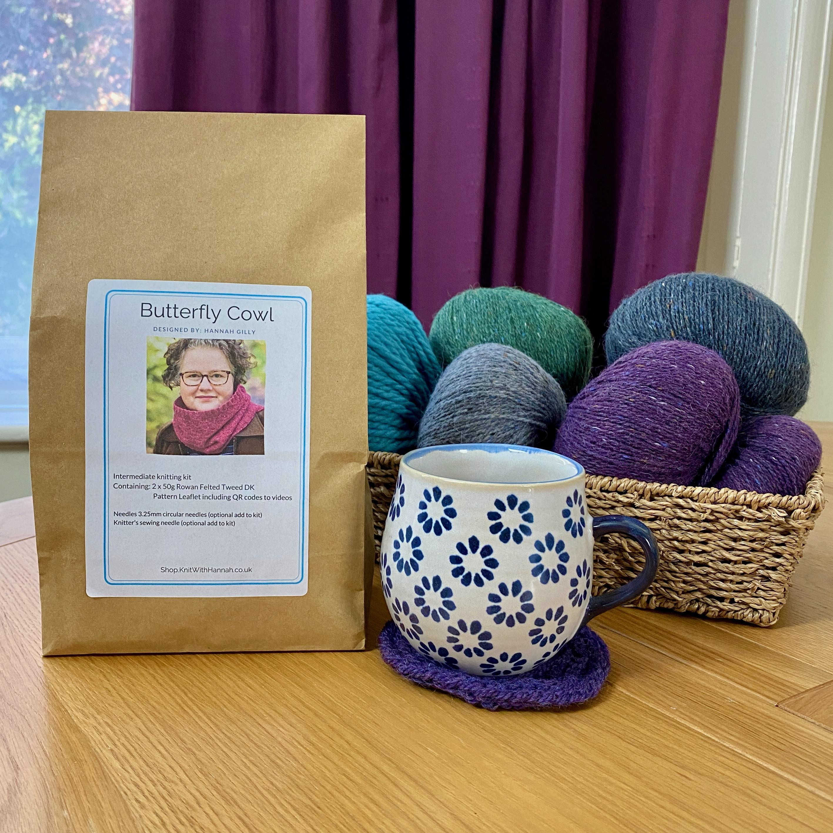 Butterfly Cowl Knitting Kit sitting on wooden table with blue & white mug of tea and