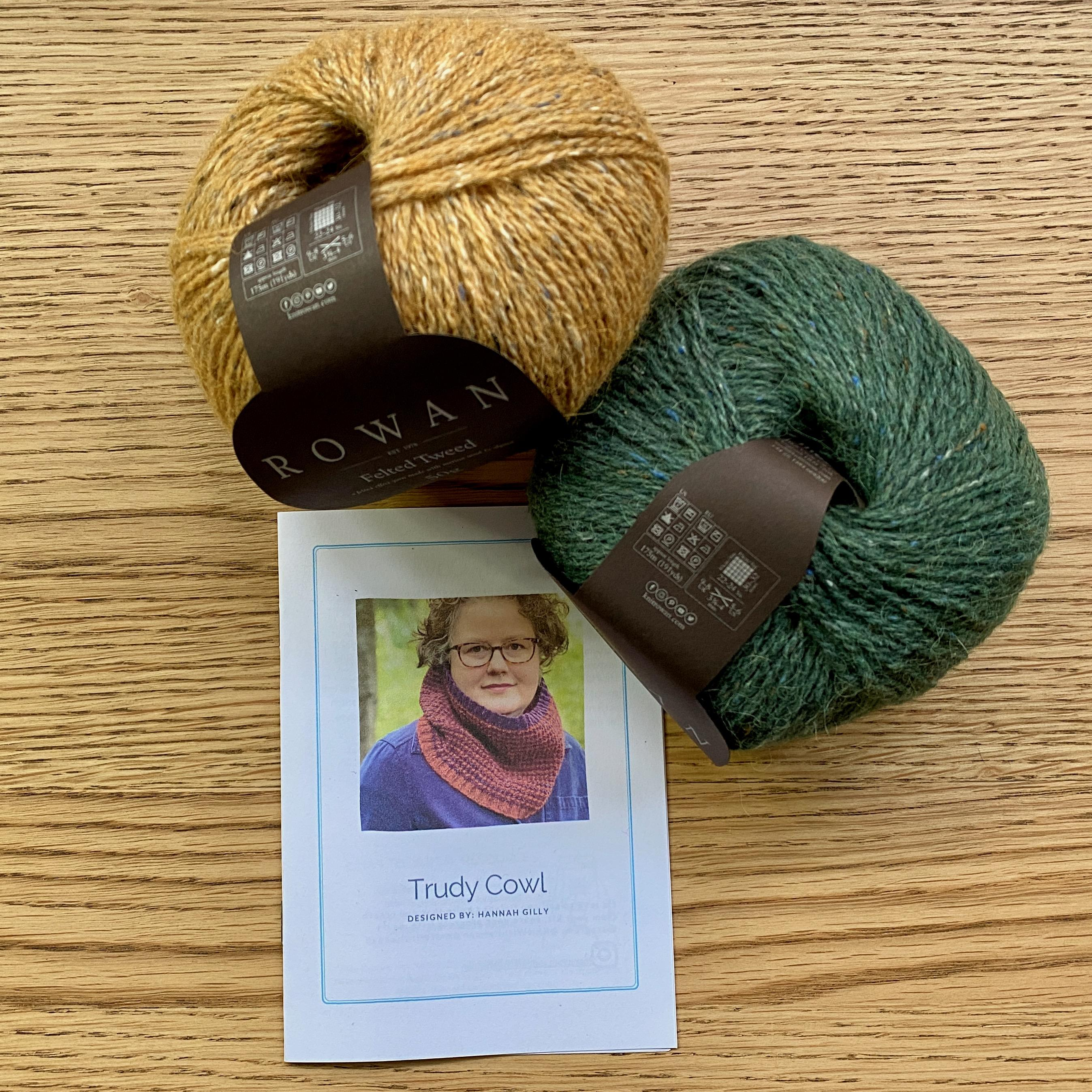 Trudy Cowl Knitting pattern on wooden table with 2 balls of yarn - cumin yellow and Pine green