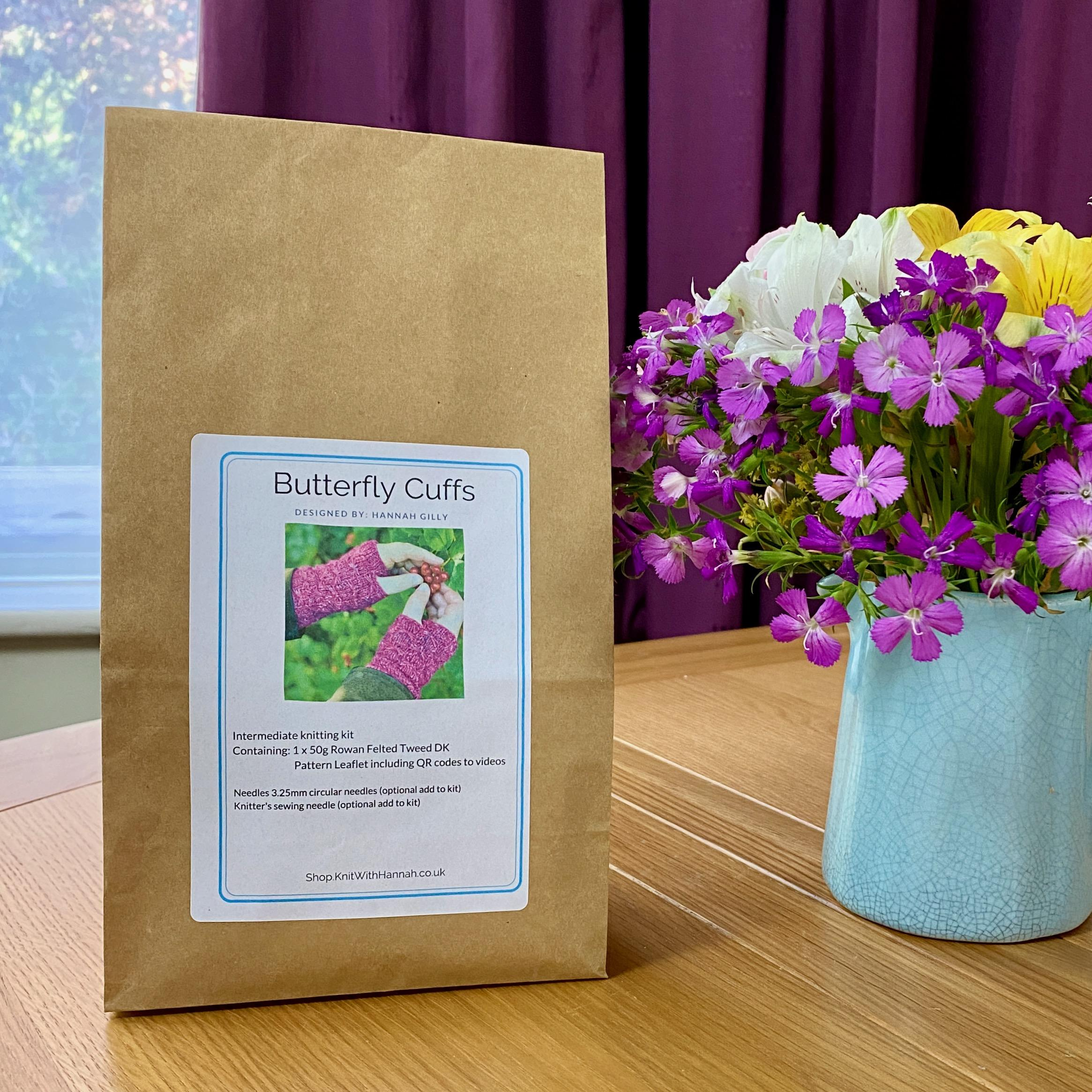 bagged knitting kit for pink butterfly cuffs kit, sitting on table with jug of pink white and yellow summer flowers