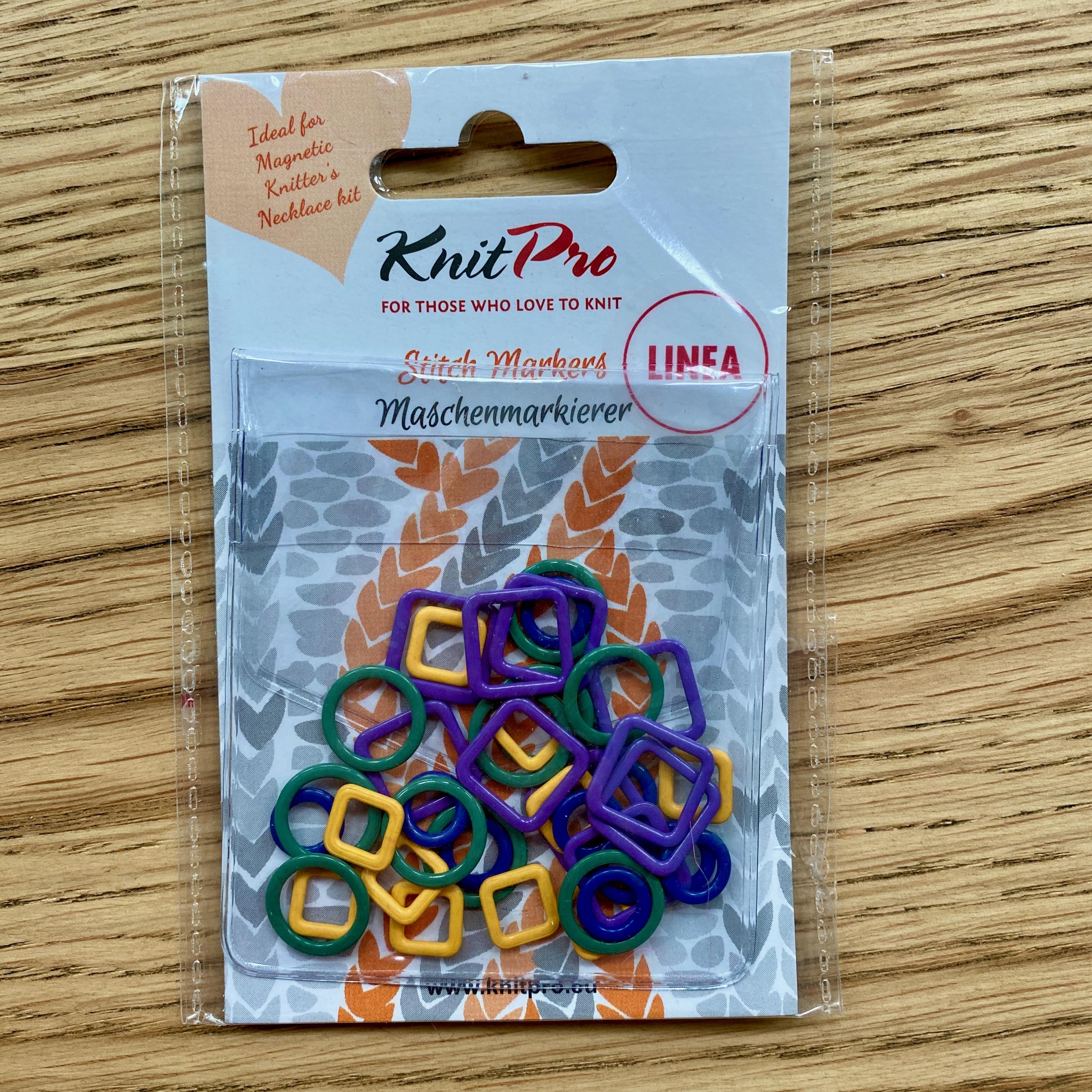 colourful metal stitch markers in plastic packaging on wooden table