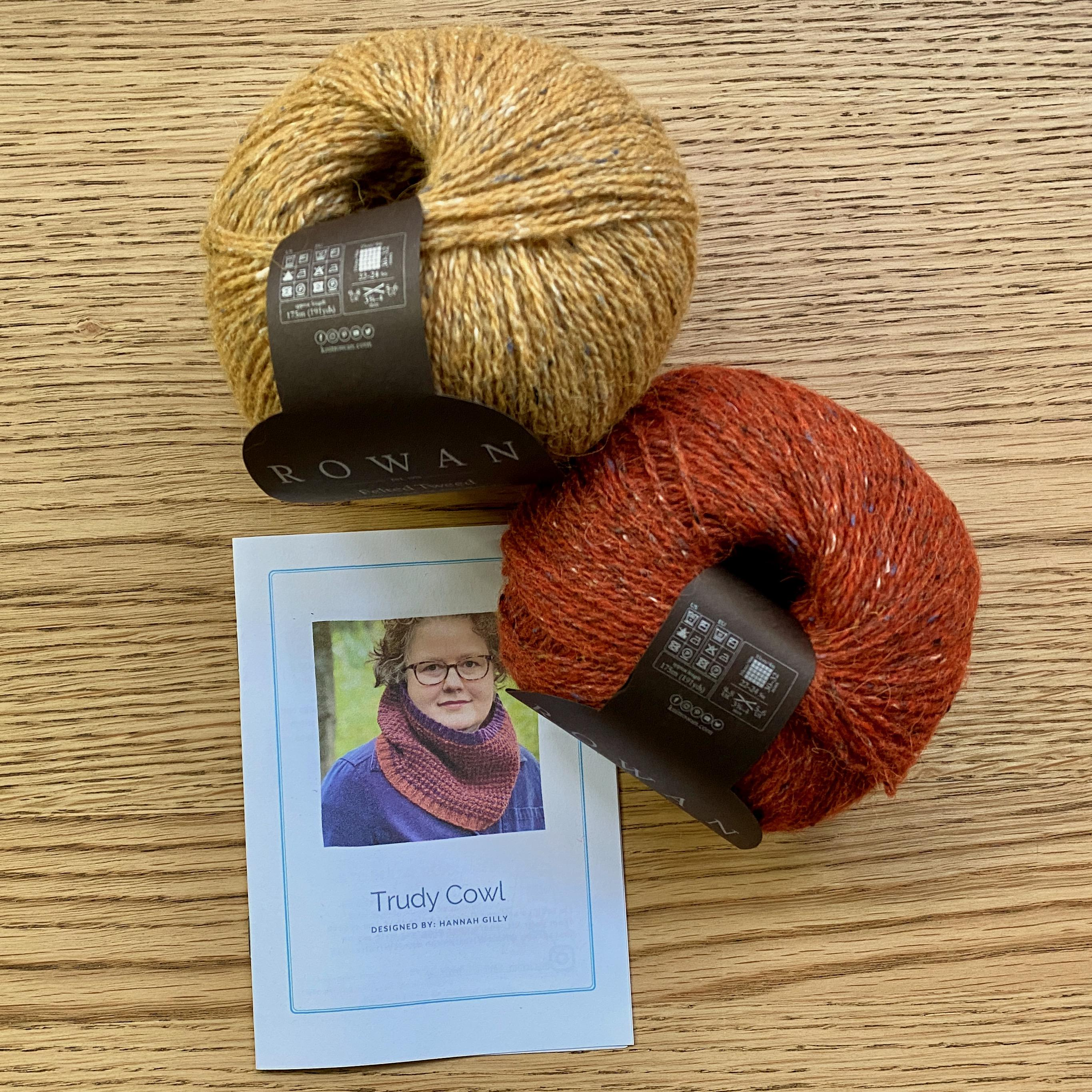Trudy Cowl Knitting pattern on wooden table with 2 balls of yarn - cumin yellow and Ginger orange