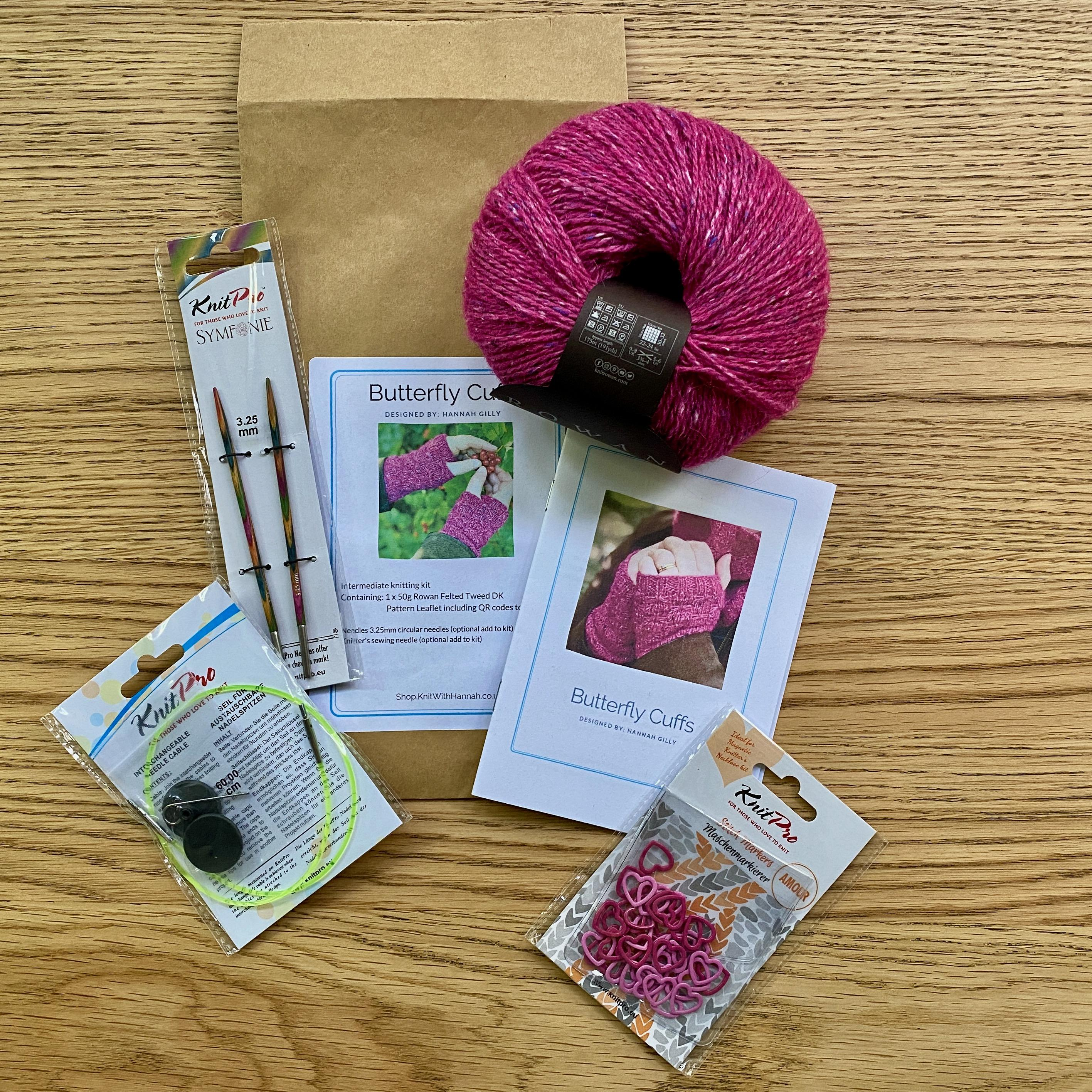 open knitting kit on wooden table, with pink yarn, pattern leaflet, circular needles and stitch markers