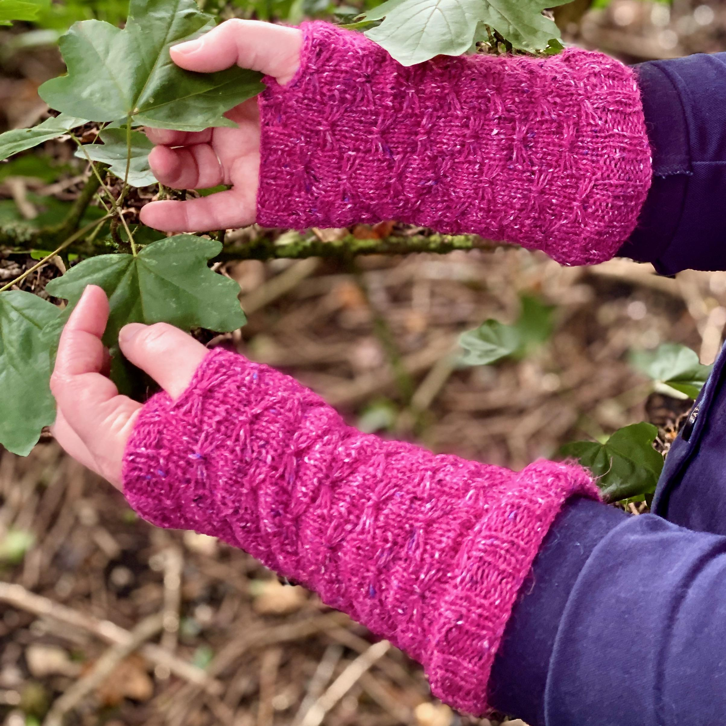 hands wearing pink knitted cuffs holding leaves on branch
