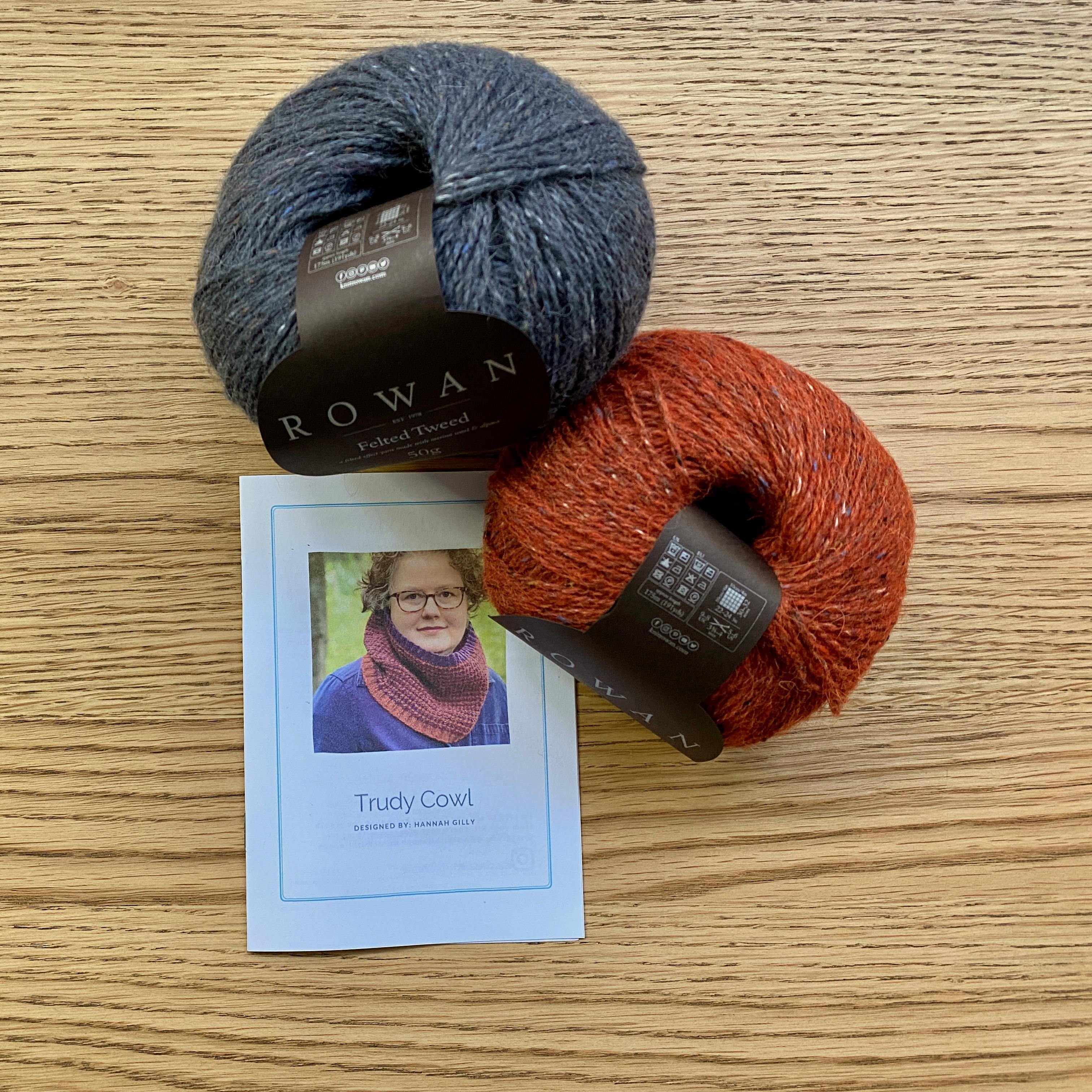 Trudy Cowl Knitting pattern on wooden table with 2 balls of yarn - ginger orange and carbon grey