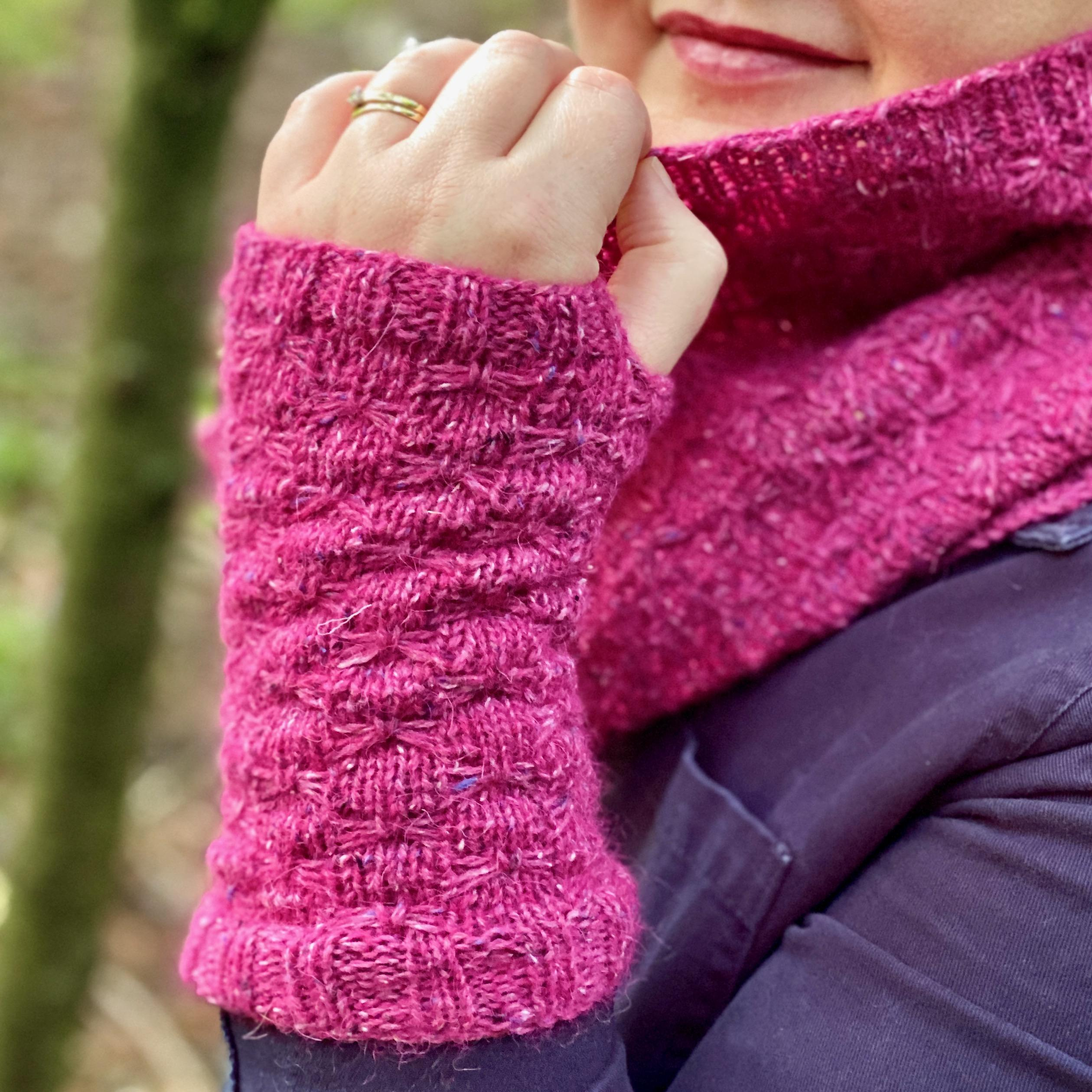 upright hand and forearm wearing pink knitted cuff