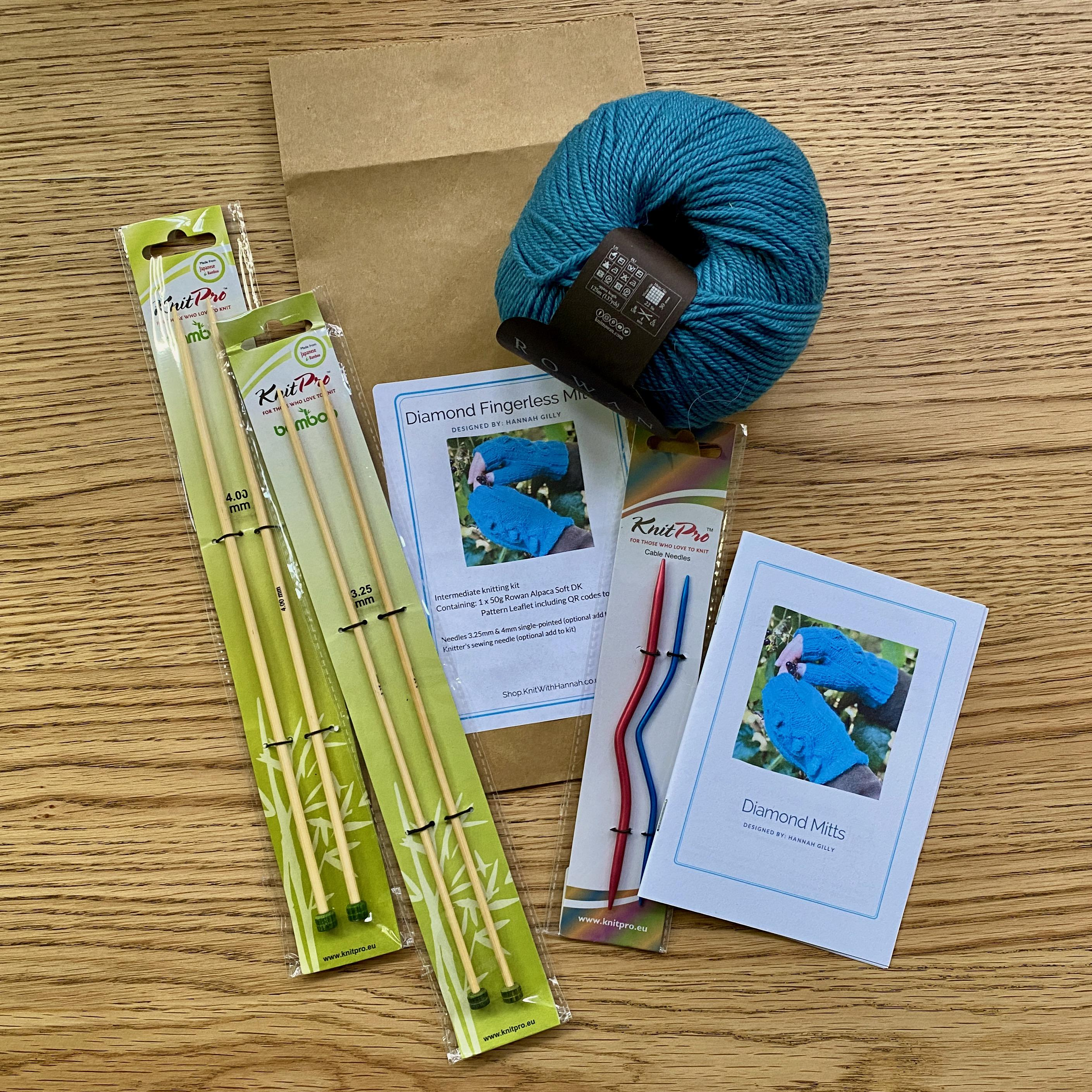 Open Knitting Kit on wooden table showing one ball of blue yarn, knitting pattern and bamboo needles