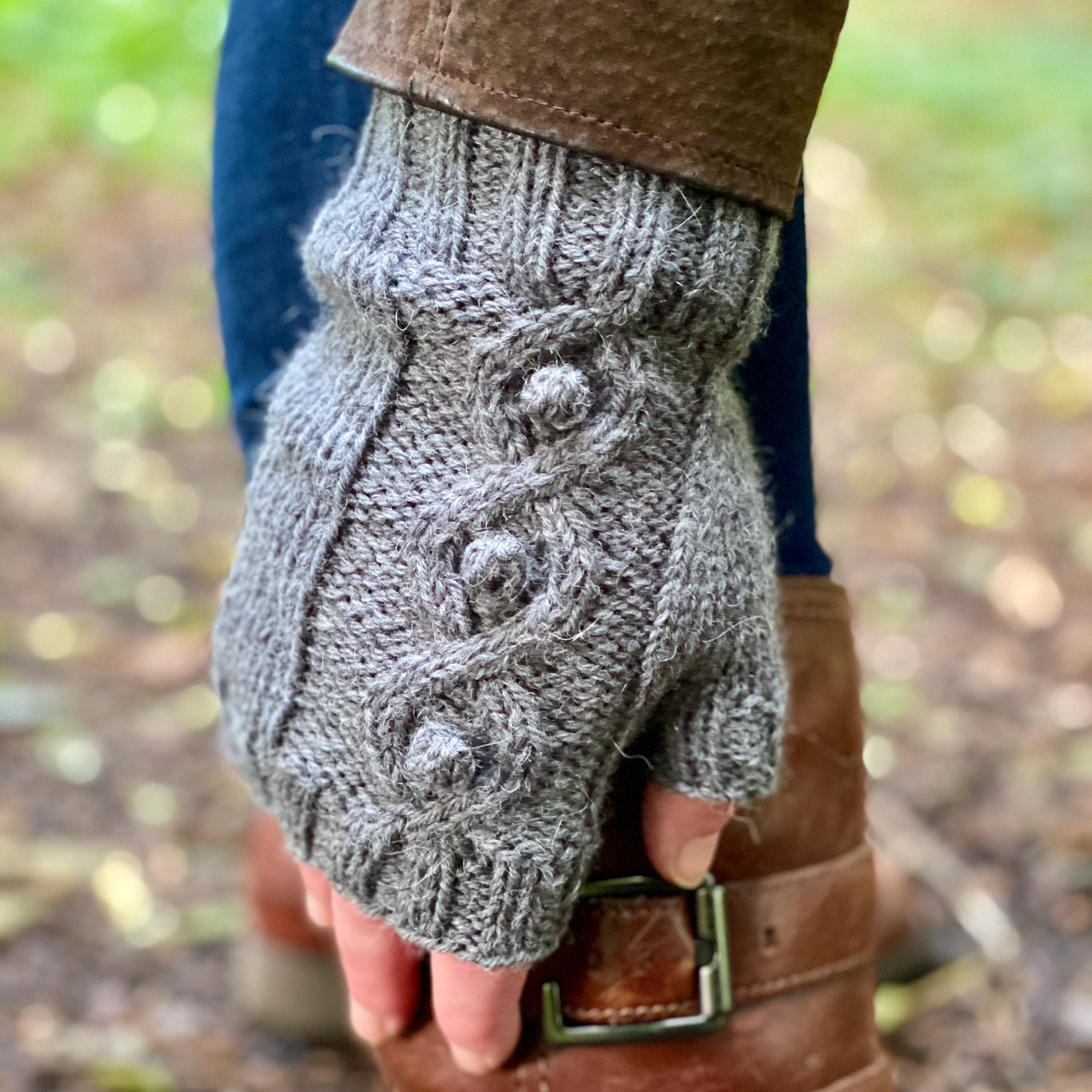 grey cabled mitt on a hand reaching down to cuff of brown leather boots