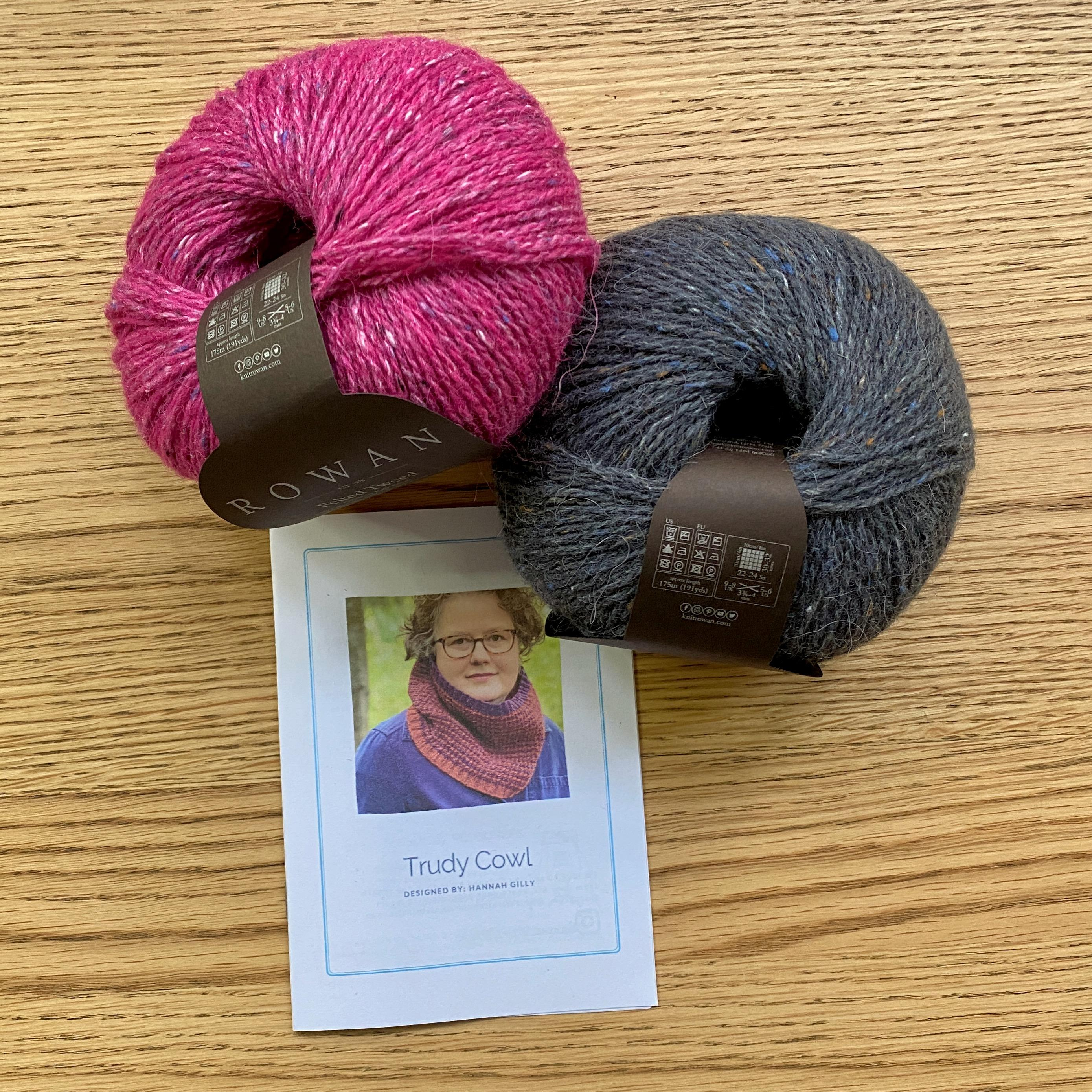Trudy Cowl Knitting pattern on wooden table with 2 balls of yarn - Bright pink and Carbon grey