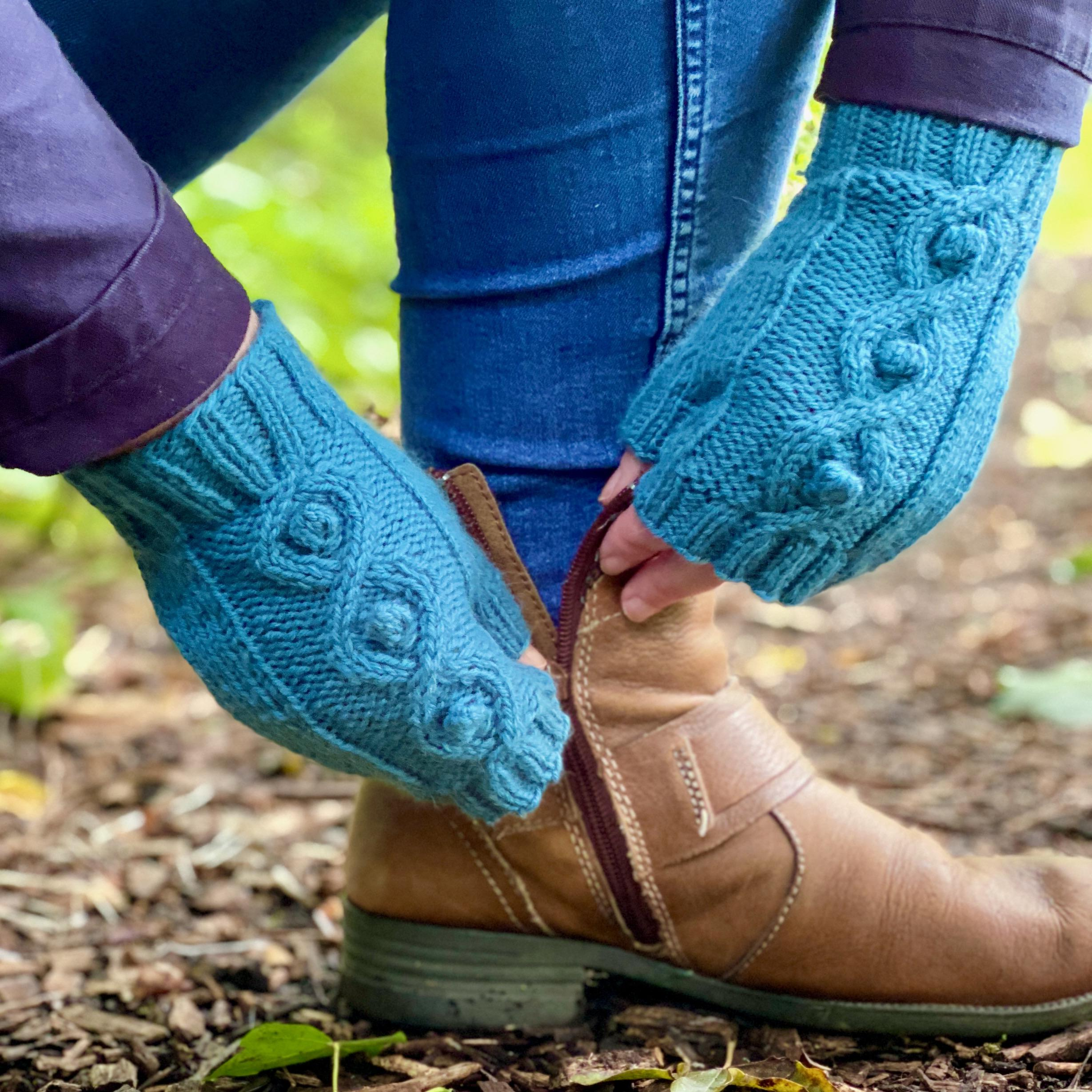 hands wearing cable mittens reaching down to fasten brown leather boots
